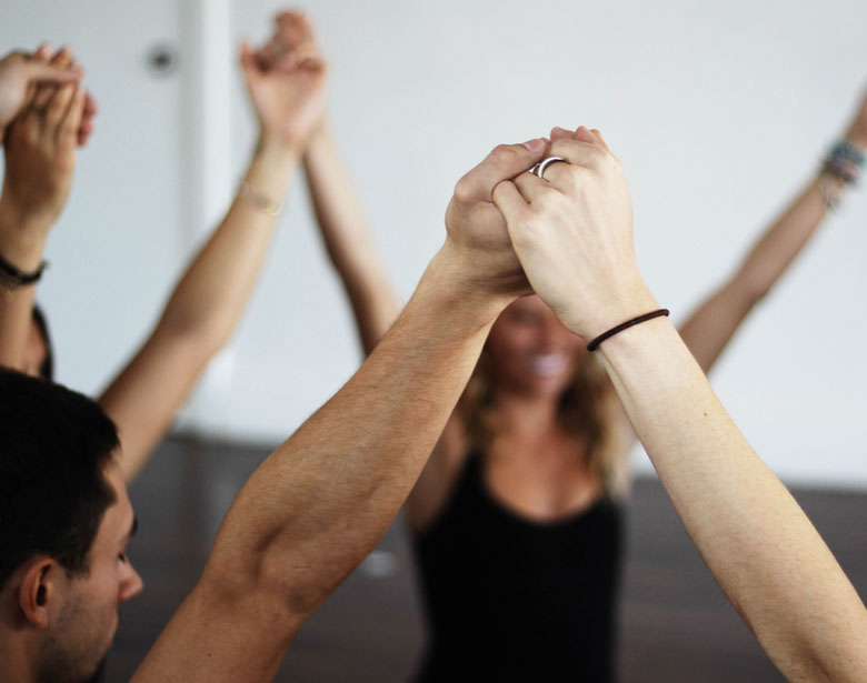 Yogis in a circle holding hands