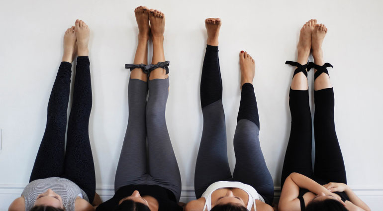 Yogis with legs up on the wall